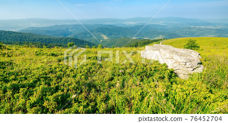 summer mountain landscape with stones on the hill. wonderful view in to the distant valley on a sunny morning. fluffy clouds above horizon 76452704