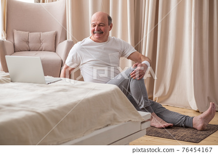 Senior caucasian man doing yoga Spine twisting pose 76454167