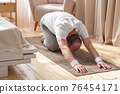 Active senior man doing the child pose while practicing yoga on a mat 76454171