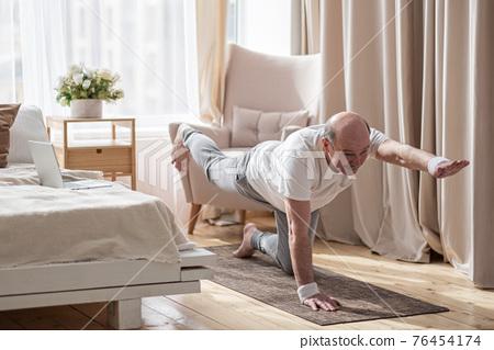 Senior caucasian men practices yoga asana chakravakasana, bird pose at home 76454174