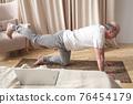 Senior caucasian men practices yoga asana chakravakasana, bird pose at home 76454179