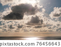 Amazing nature Sky of dramatic clouds with lens flare in a blue sky as a fluffy white cloud approaches and obscures it sending light rays and shadows from the cloud nature background 76456643