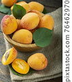 Ripe apricot with leaves in a bowl on a wooden table. Home harvest from your own garden. 76462970