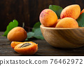 Ripe apricots and apricot leaves in a bowl on a wooden table. Fresh fruits from the home garden. 76462972