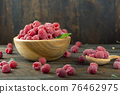Fresh raspberries in a wooden plate with leaves. The berries are scattered on a wooden table. 76462975