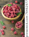 Fresh raspberries in a wooden plate with leaves. The berries are scattered on a wooden table. 76462977