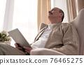 Senior man websurfing on internet with digital tablet sitting at home 76465275