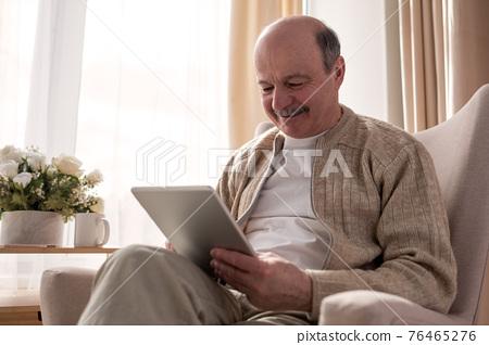 Senior man websurfing on internet with digital tablet sitting at home 76465276