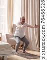 Senior man practicing yoga at home doing Chair pose, Utkatasana 76466526