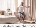 Senior man practicing yoga at home doing Chair pose, Utkatasana 76466527