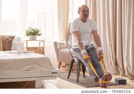 Man sitting on chair doing paschimottanasana or Intense Dorsal Stretch pose 76466528