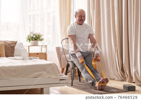 Man sitting on chair doing paschimottanasana or Intense Dorsal Stretch pose 76466529