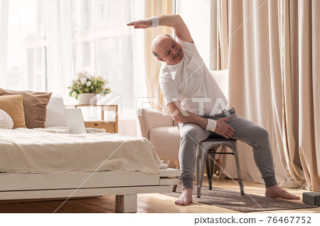 Senior caucasian man stretching side sitting on chair at his living room. 76467752