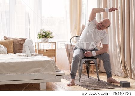 Senior caucasian man stretching side sitting on chair at his living room. 76467753