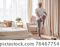 Elderly man practicing yoga or fitness standing on tree pose at home. 76467754