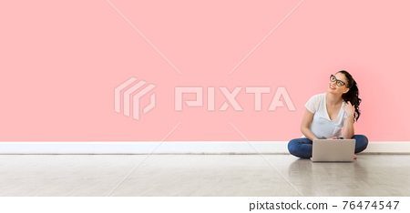 Young woman using her laptop 76474547