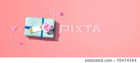 Gift box with a pink carnation flower 76474564