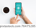 Lady holding smartphone with Immune digital passport for covid-19 76475285
