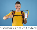 Tourist showing smartphone with Immune digital passport for covid-19 76475670
