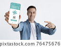 Young guy showing smartphone with Immune digital passport for covid 76475676