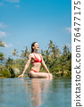 Woman in tropical vacation sitting in the water of pool 76477175