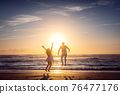 Couple on honeymoon during sunset on the beach jumping high 76477176
