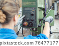 Woman worker in metal workshop operating power drill 76477177