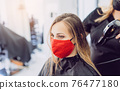 Woman wearing red face mask getting fresh styling at a hairdresser 76477180