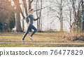 Woman running with face mask to stay healthy during covid-19 76477829