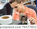 Woman working on label printing machine 76477832