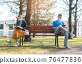 Woman and man in social distancing sitting on bench 76477836