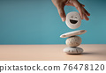 Enjoying Life Concept. Harmony and Positive Mind. Hand Setting White Natural Stone Stack to Balance. Balancing Body, Mind, Soul and Spirit. Mental Health Practice 76478120