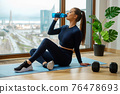 Brunette woman in tracksuit drinks water by panoramic window 76478693