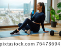 Woman with water bottle in hand sits on blue mat near window 76478694