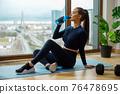 Slender woman drinks water near window on glazed balcony 76478695
