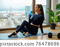 Woman with water bottle in hand in resting pose near window 76478696
