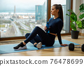 Sportive brunette with water bottle in hand sits on mat 76478699
