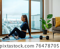 Brunette with ponytail practices yoga on glazed balcony 76478705