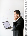 concentrated investment manager talking on phone and drinks coffee 76478827