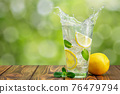 lemonade in glass on wooden table with green blurred background 76479794