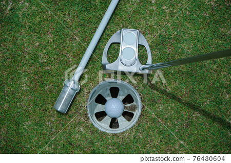 Golf ball is beside the hole. Golf ball on the edge of hole on the green grass 76480604