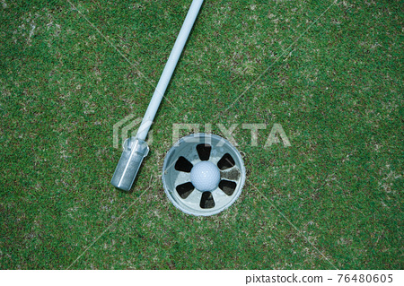 Golf ball is beside the hole. Golf ball on the edge of hole on the green grass 76480605