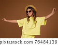 cute curly girl in hat and sunglasses 76484139