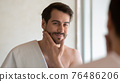 Smiling young Caucasian man look in mirror in bathroom 76486206