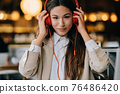 Young woman with headphones listen music while sitting in cafes 76486420