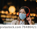 A girl sitting in a coffee shop with headphones. Coronavirus outbreak. 76486421