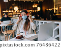 A girl sitting in a coffee shop with headphones. Coronavirus outbreak. 76486422