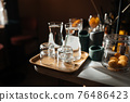 Four glass cups on the bar counter with serving accessories. 76486423