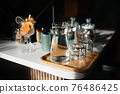 Four glass cups on the bar counter with serving accessories. 76486425