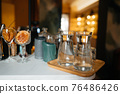 Four glass cups on the bar counter with serving accessories. 76486426